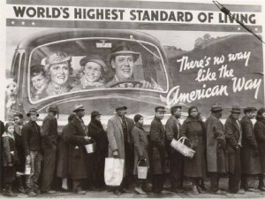 picture of a depression-era soup line in front of a billboard depicting the great american way
